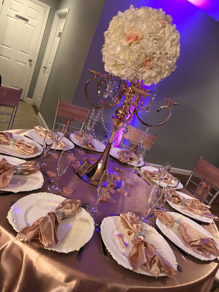 round table with satin tan table cloth and tall floral arrangement