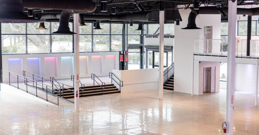 interior event space with wood floors, large windows, white columns and black ceiling