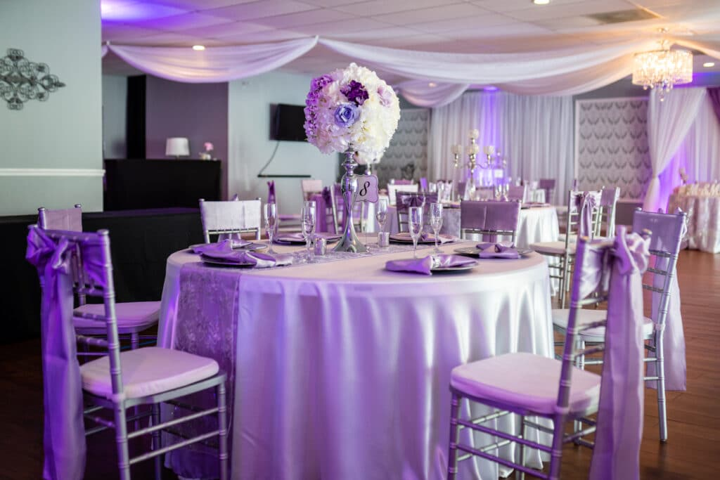 white and purple wedding decor with round tables and tall floral arrangements