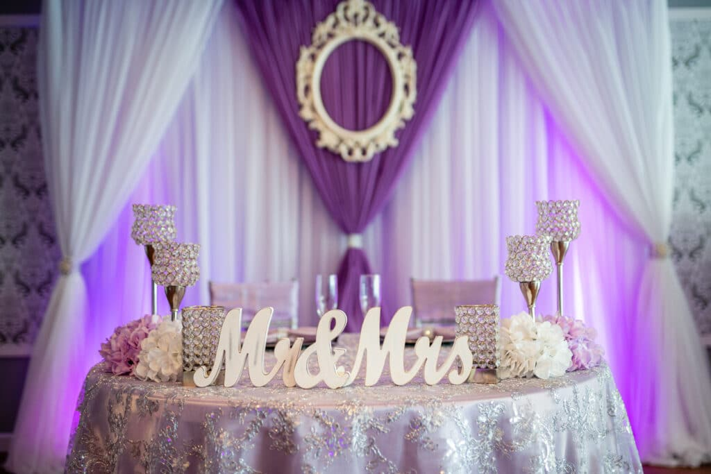 white canopy with purple lighting over sweetheart table with mr and mrs sign