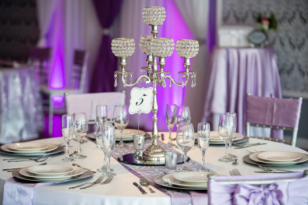 table with purple linens white dishes and silver candelabra