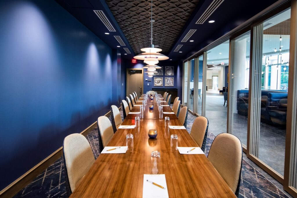 long wood table with brown chairs in conference room with blue wall on one side and windows on the other
