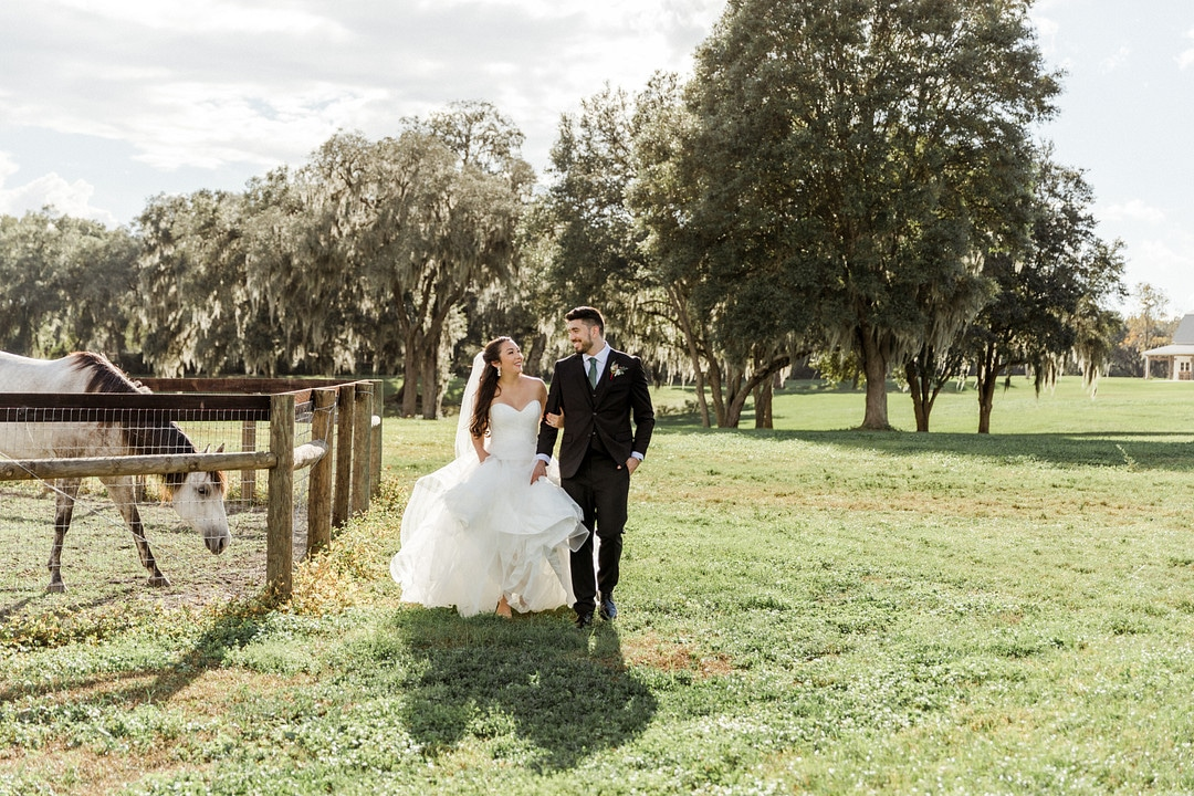 bride holds arm of groom while walking next to him outside surrounded by grass and trees at wedding venue