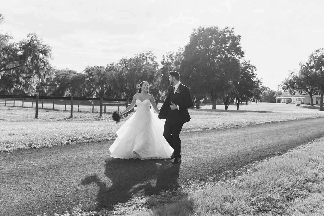 black and white image of bride and groom walking down a road surrounded by grass and trees laughing