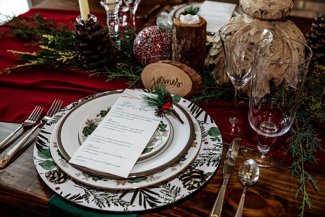 close up of tableware setup with christmas plates and a wood slice as a place card for guest