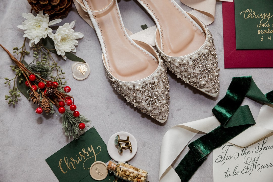 pointed wedding shoes with bling next to custom groom cuff links surrounded by floral decor pieces and other hand written calligraphy wedding pieces