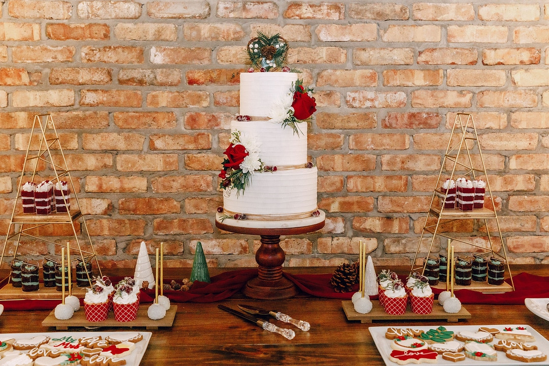 wedding cake table display surrounded by cake cutting set and festive desserts including cupcakes and cake pops