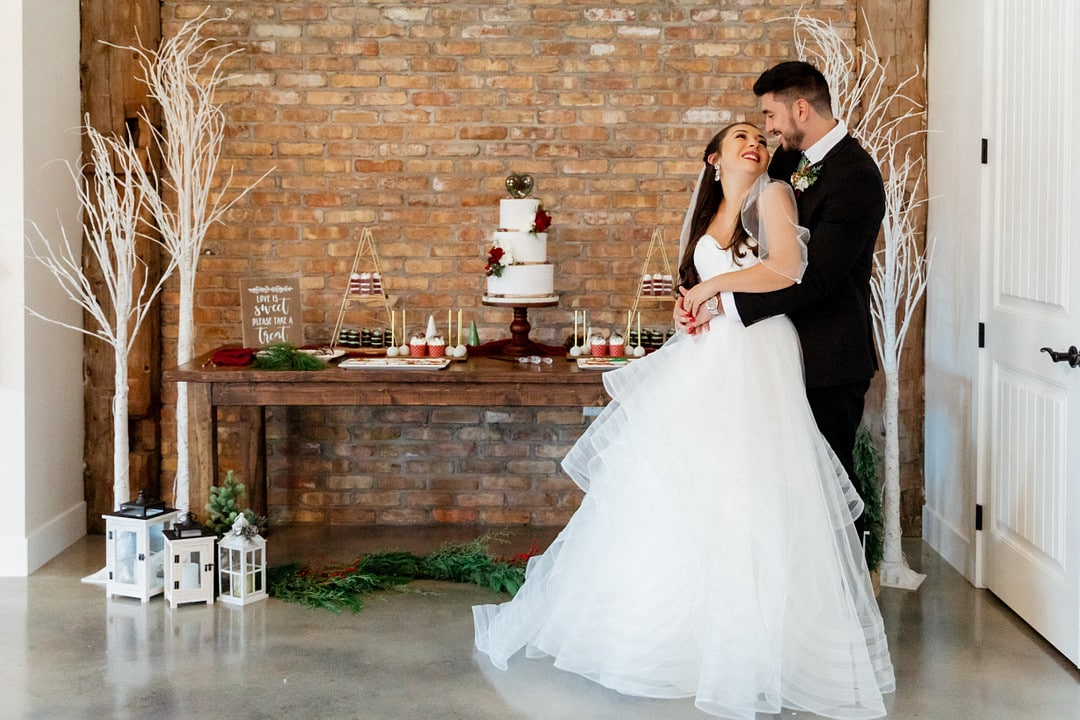 bride and groom stand in front of romantic christmas wedding dessert table with garland and lanterns