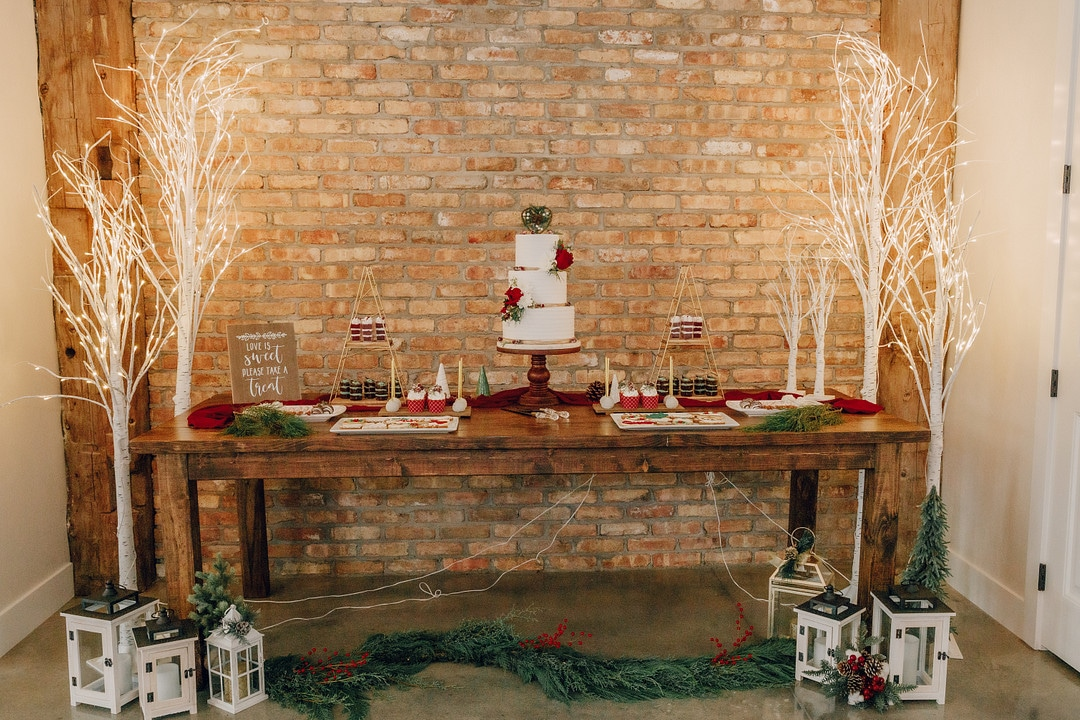 cake sitting on farm wood table with garland and lanterns on the floor in front of it and the cake surrounded by other christmas desserts