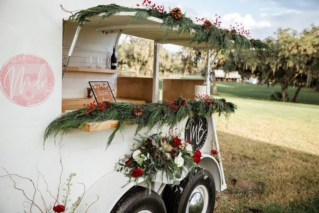 mobile bar outside of wedding venue decorated with a large floral piece and garland with cranberries and pinecones mixed in