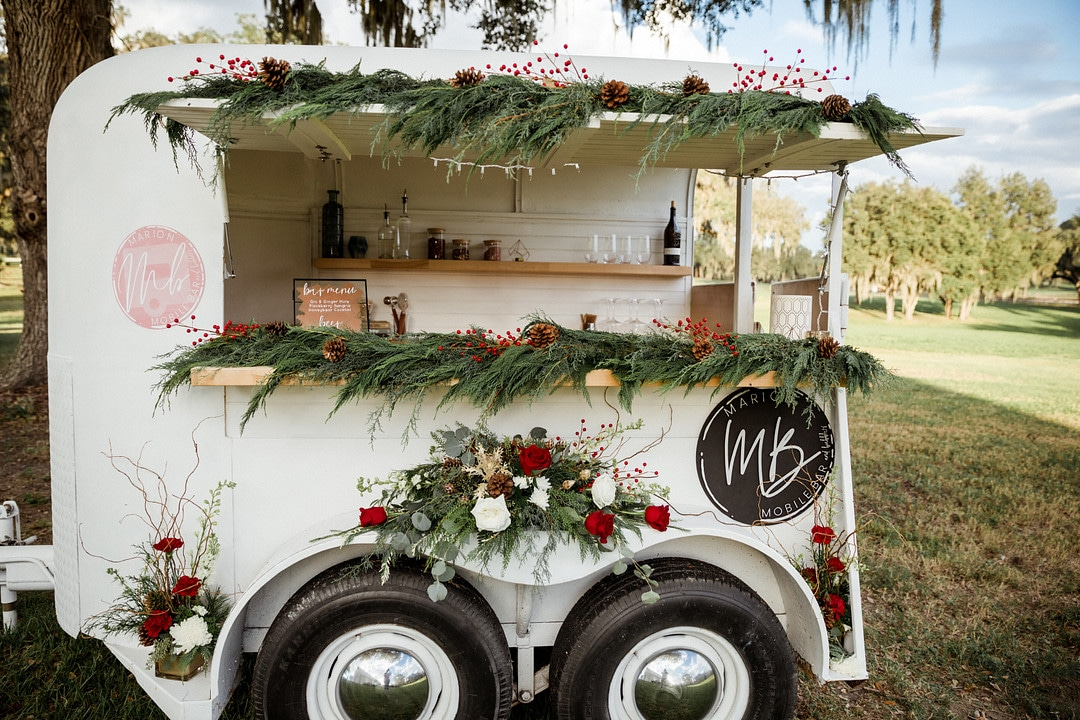 wedding mobile bar outside at wedding venue decorated for a romantic christmas wedding with floral and garland pieces