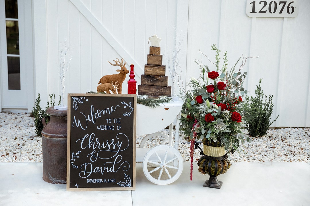 handwritten welcome sign for wedding outside with huge christmas floral arrangement with other wooden and rustic christmas decor next to it