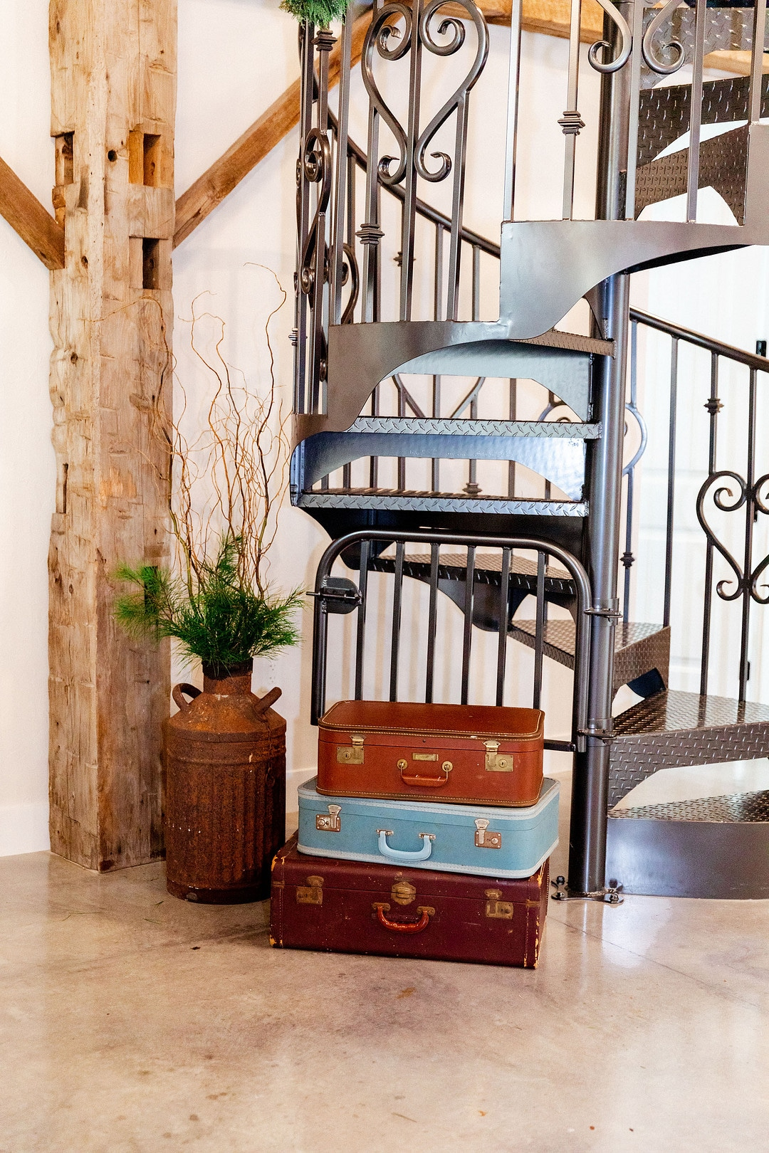 spiral staircase with three suitcases in front of it stacked on top of each other