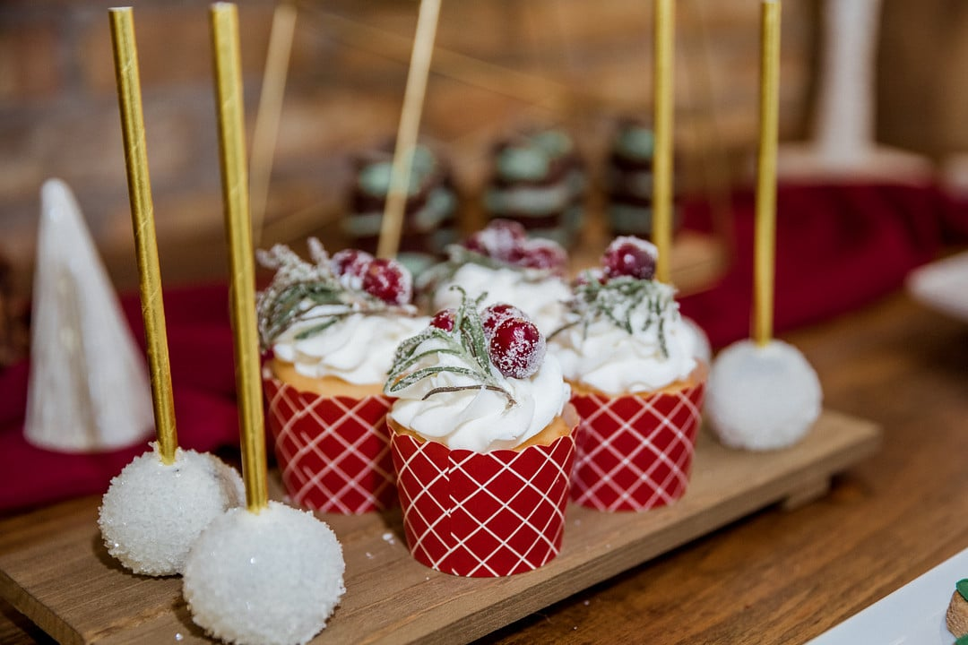 close up of four cupcakes with white buttercream frosting topped with frosted cranberries and sprigs of greenery next to sparkly cake pops with gold sticks
