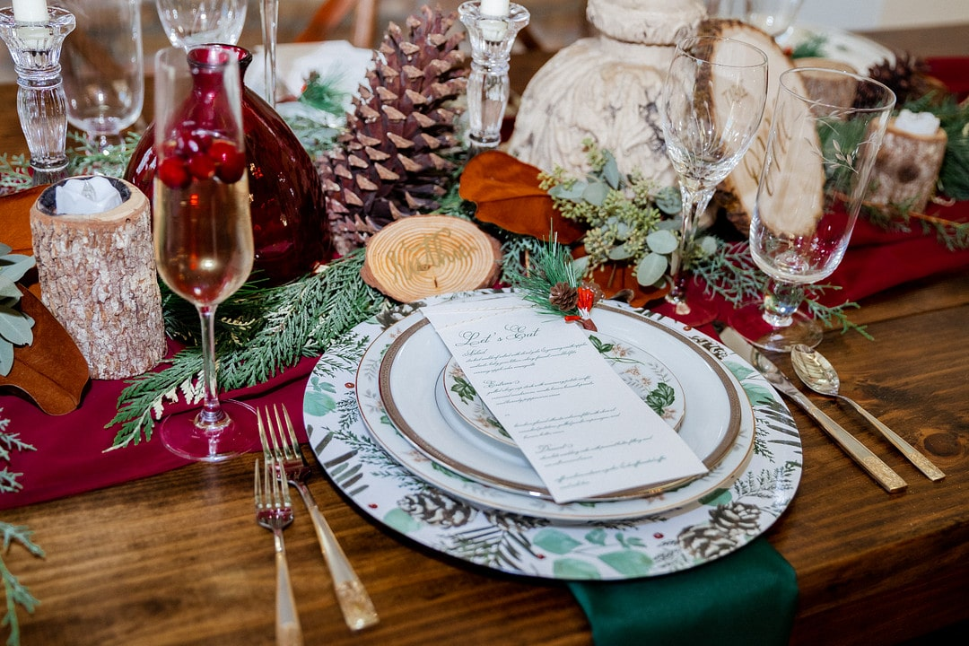 romantic christmas wedding table decor with pinecones and wood slices combined with candles and greenery from pine trees