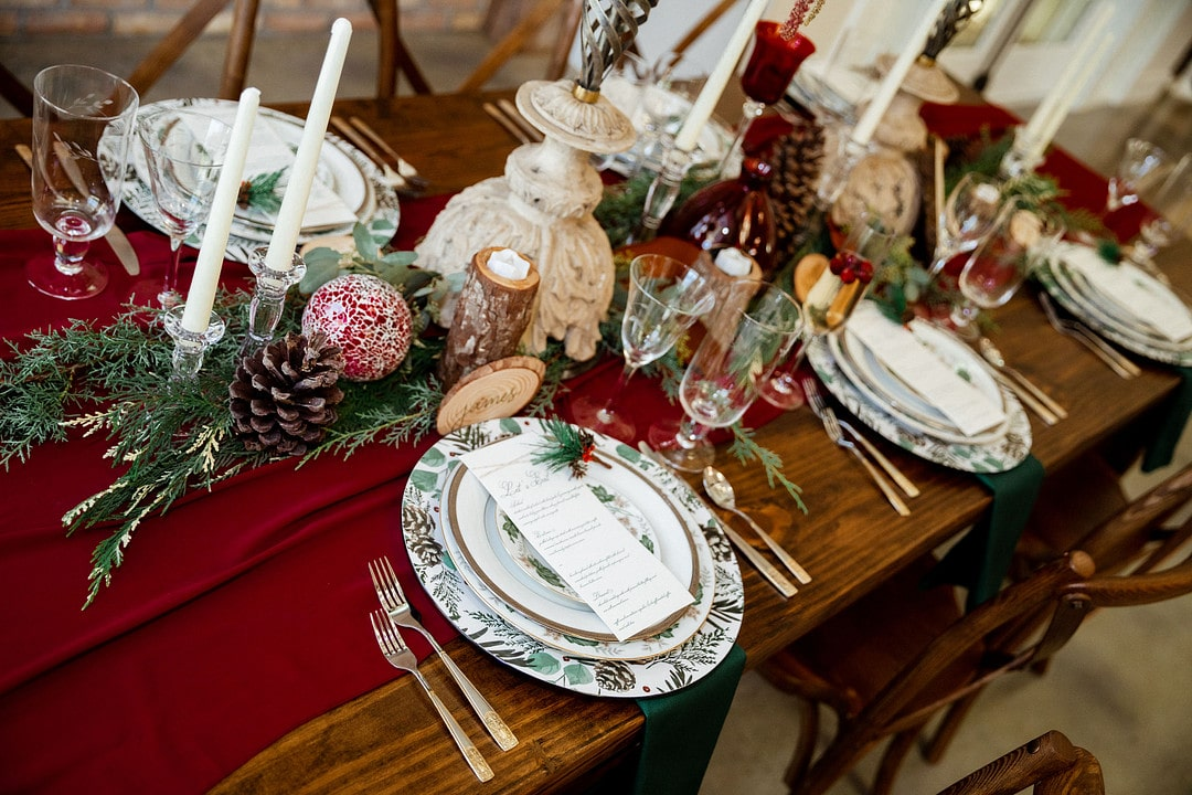 long shot of table set up inspired by christmas with glasses plates silverware and decor in the middle on top of red cloth down the center of the table