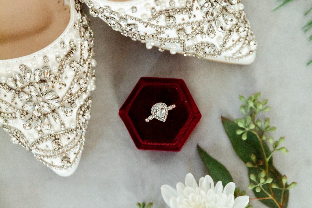 unique shapped red velvet ring box with tear drop style wedding ring inside next to the white wedding heels that have a lot of bling