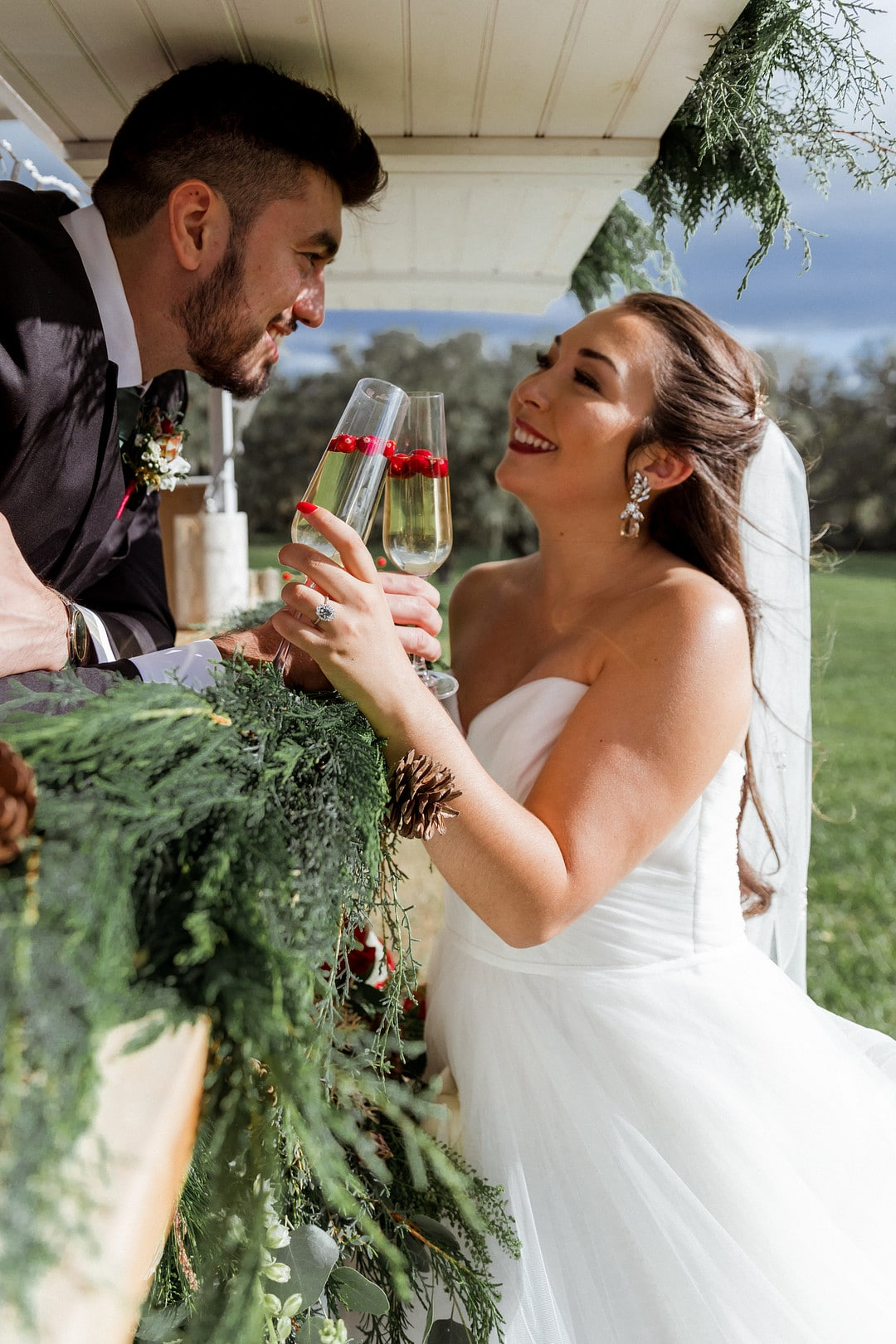 groom in mobile bar toasting champagne with cranberries in glass with his bride wearing a veil