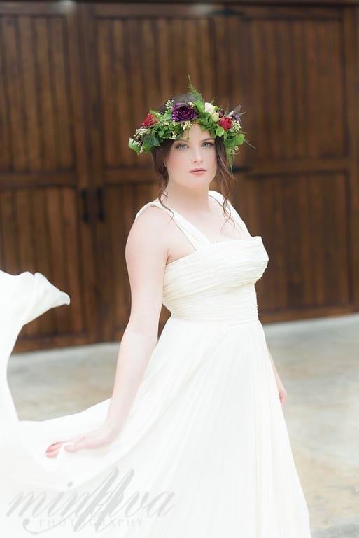 bride with flower crown standing in front of dark wooden doors
