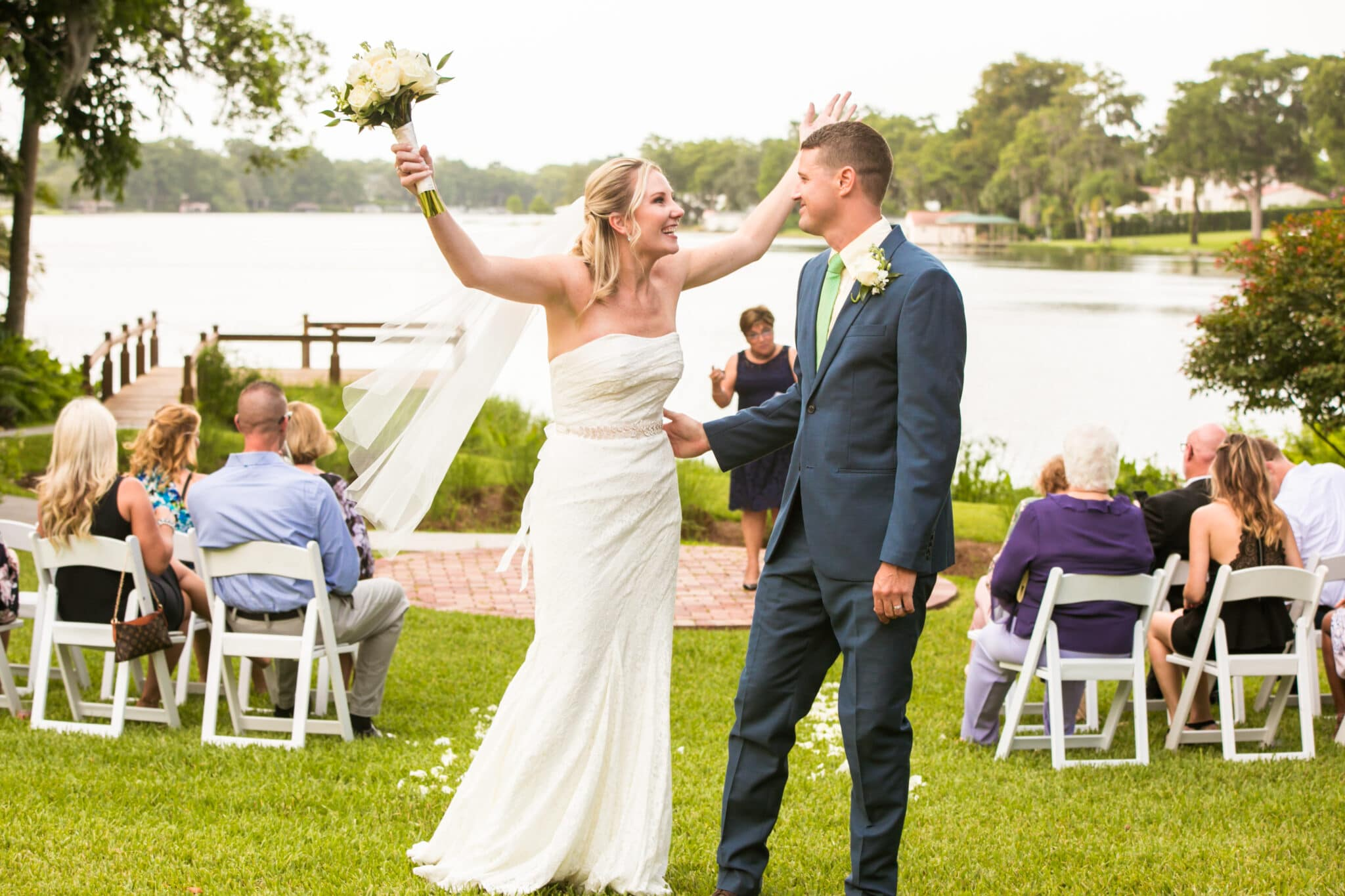 bride and groom at end of the aisle looking at each other in front of lake and ceremony space with brides arm thrown up holding bouquet