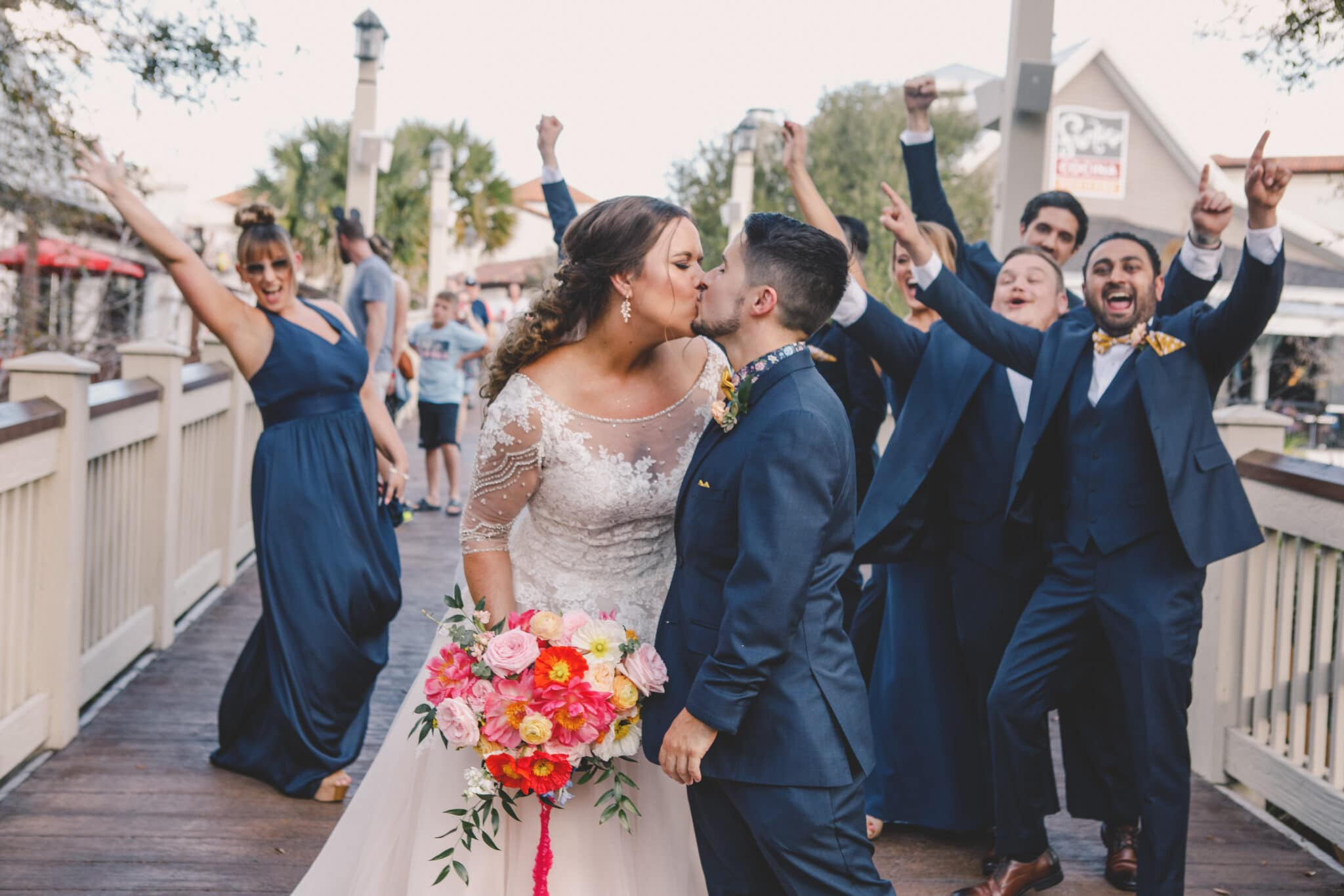 bride and groom kissing on boardwalk while bride holding bright colored bouquet in front of bridal party excited wearing navy blue attire