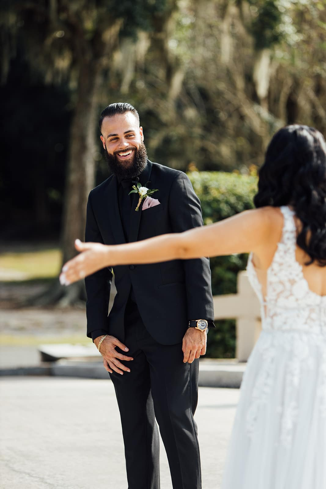 bride walks over to groom with arm out and lace wedding gown on groom dressed in black tux with beard