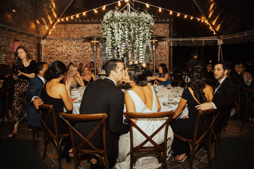 outdoor wedding reception with hanging floral chandelier in clear tent bride and groom sit in wooden cross back chairs kissing