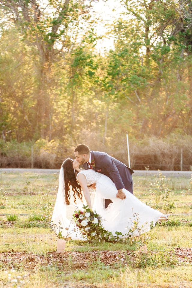 groom dips bride down while she holds her bouquet in one hand and they kiss outside during sunset