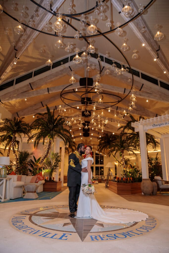 bride and groom on compass floor at margaritaville resort orlando with unique lighting fixture above them
