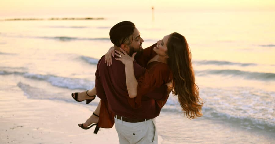 fiance carrying his future bride on the beach at sunset moments after proposing