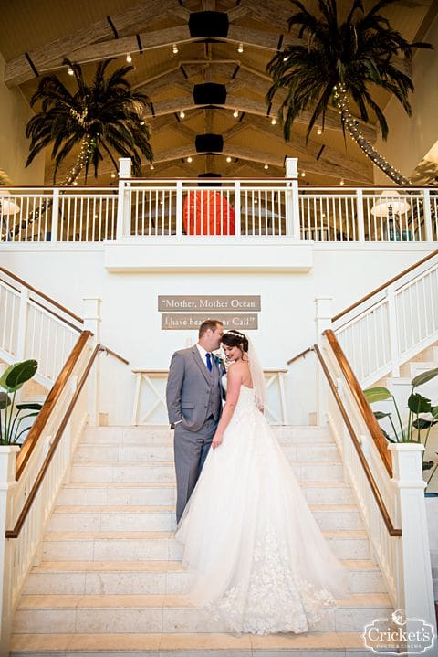bride and groom on staircase with palm trees in background - margaritaville resort orlando