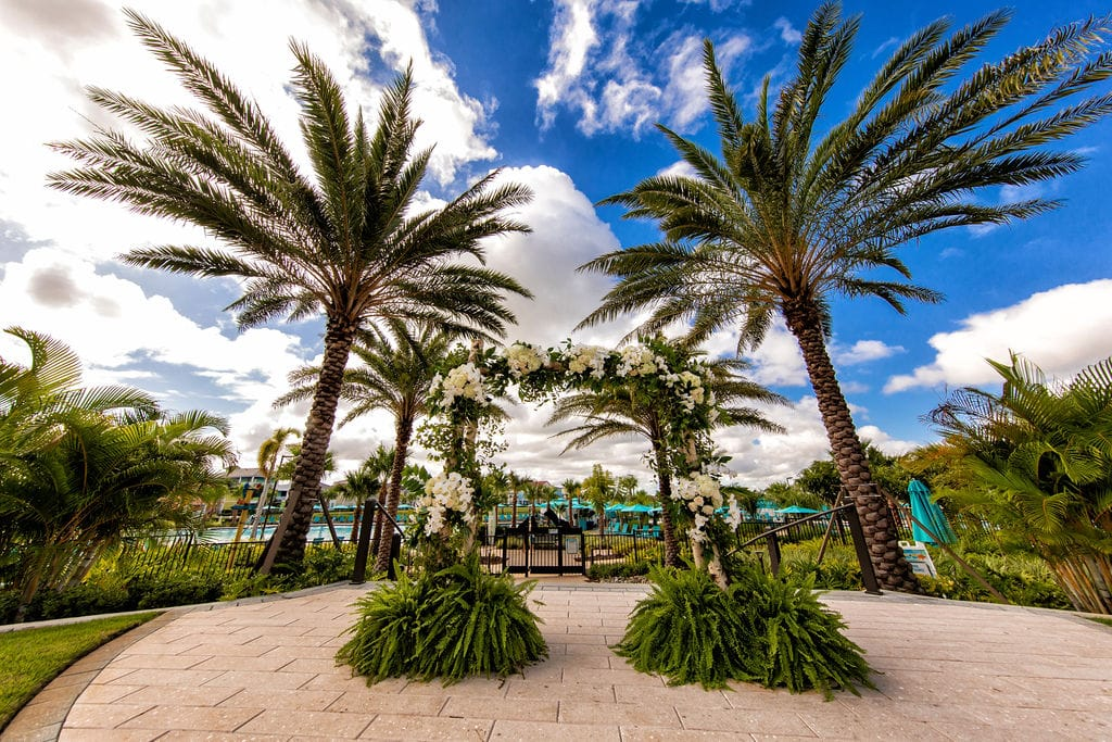 patio with palm trees and floral arch for wedding ceremony - margaritaville resort orlando wedding venue