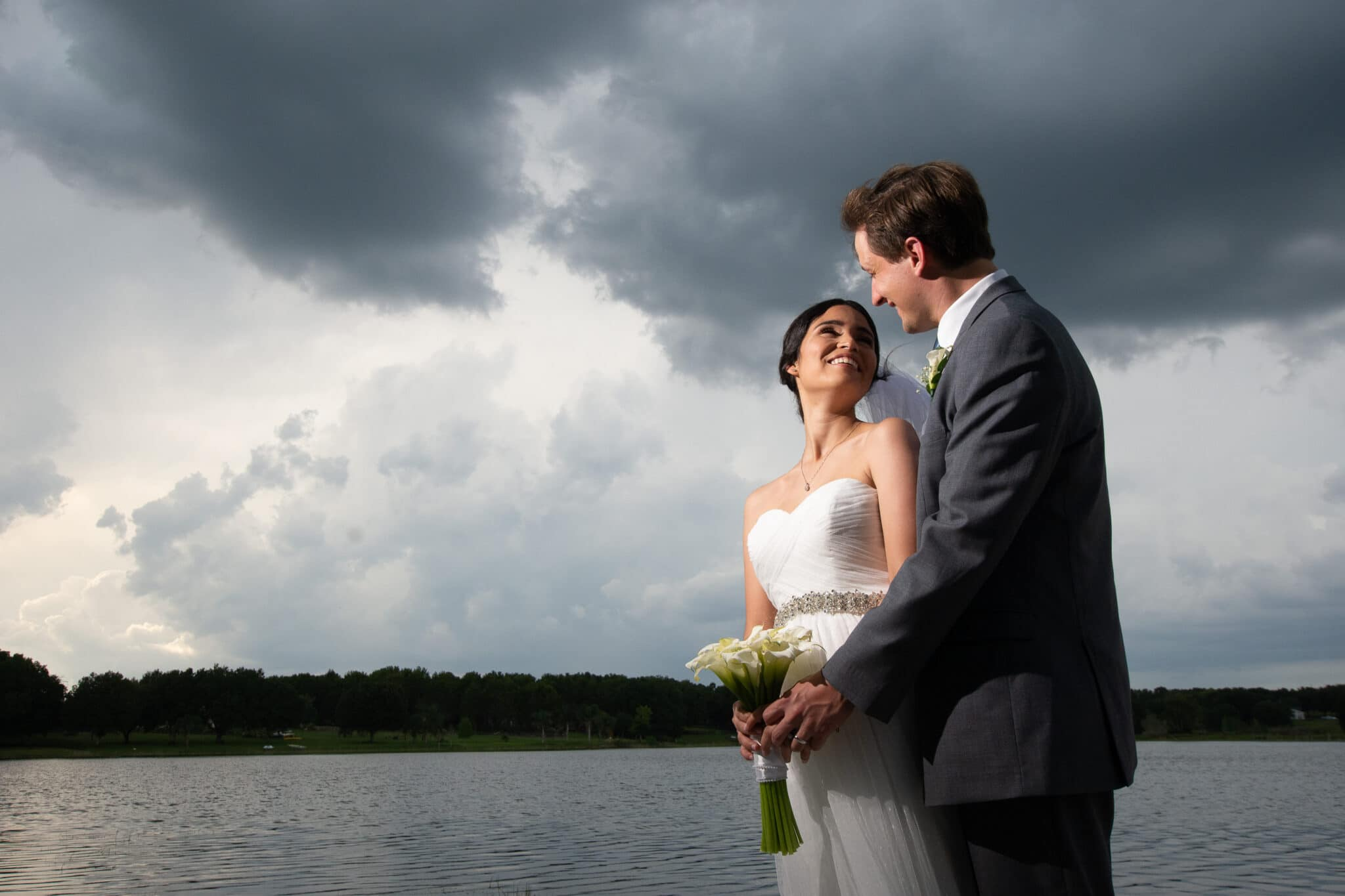 bride and groom by water under clouds
