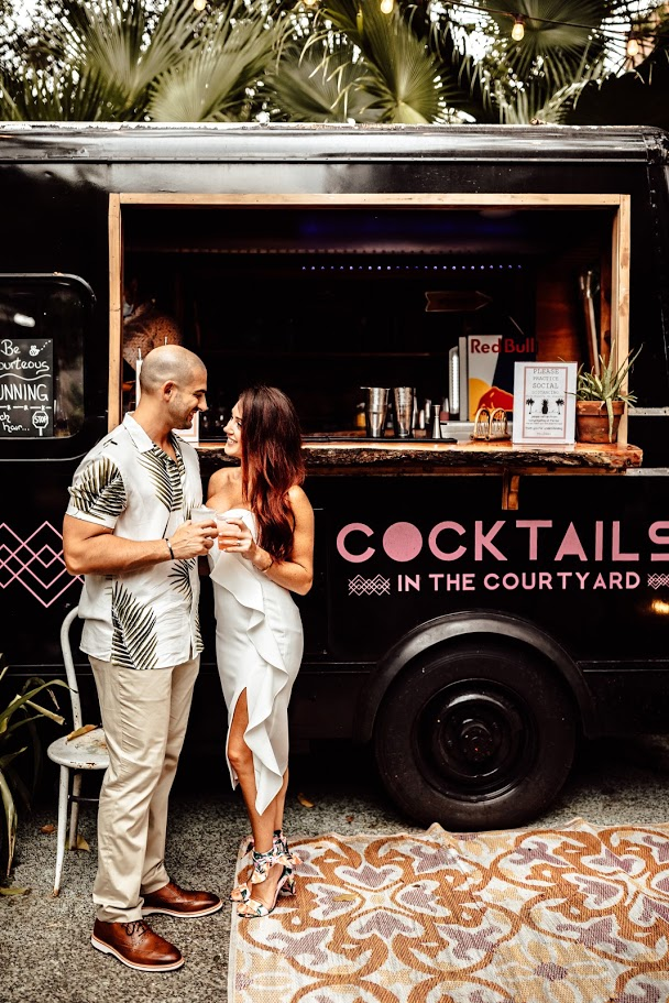 man and woman toasting glasses in front of black cocktails truck with pink lettering