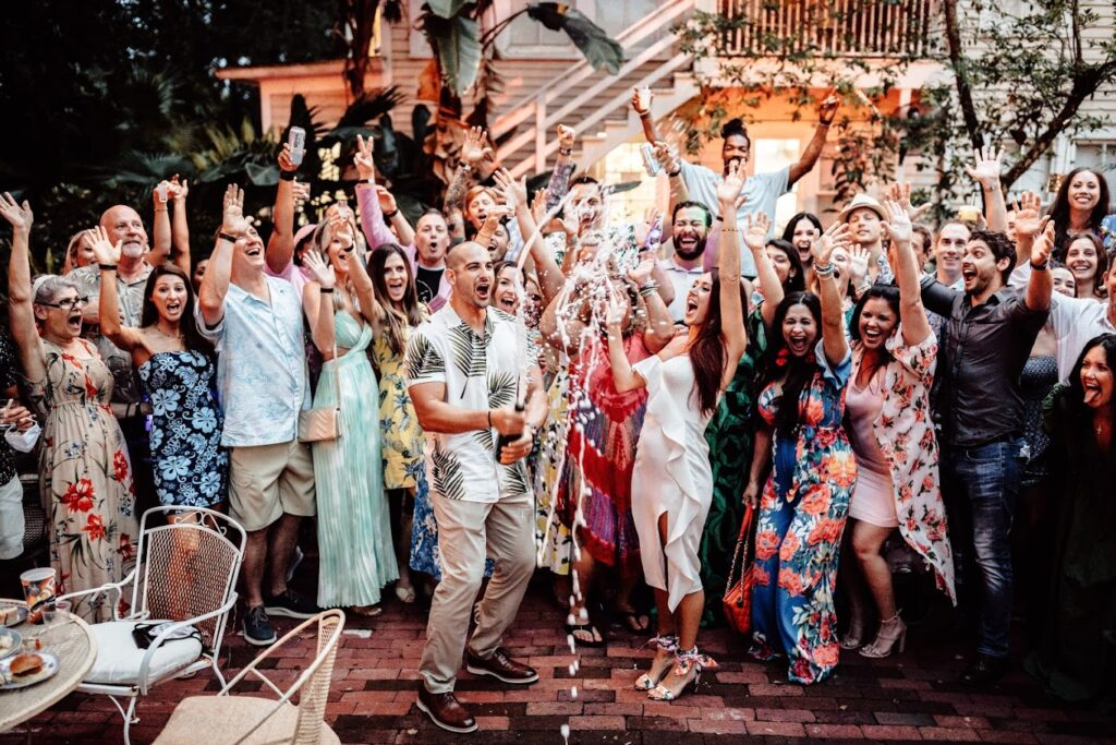 group of people celebrating while man pops champagne bottle at casual outdoor wedding reception