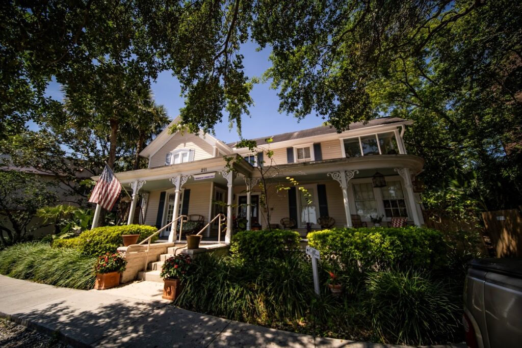 white house with porch, steps, flag, and beautiful landscaping at wellborn wedding venue in central florida