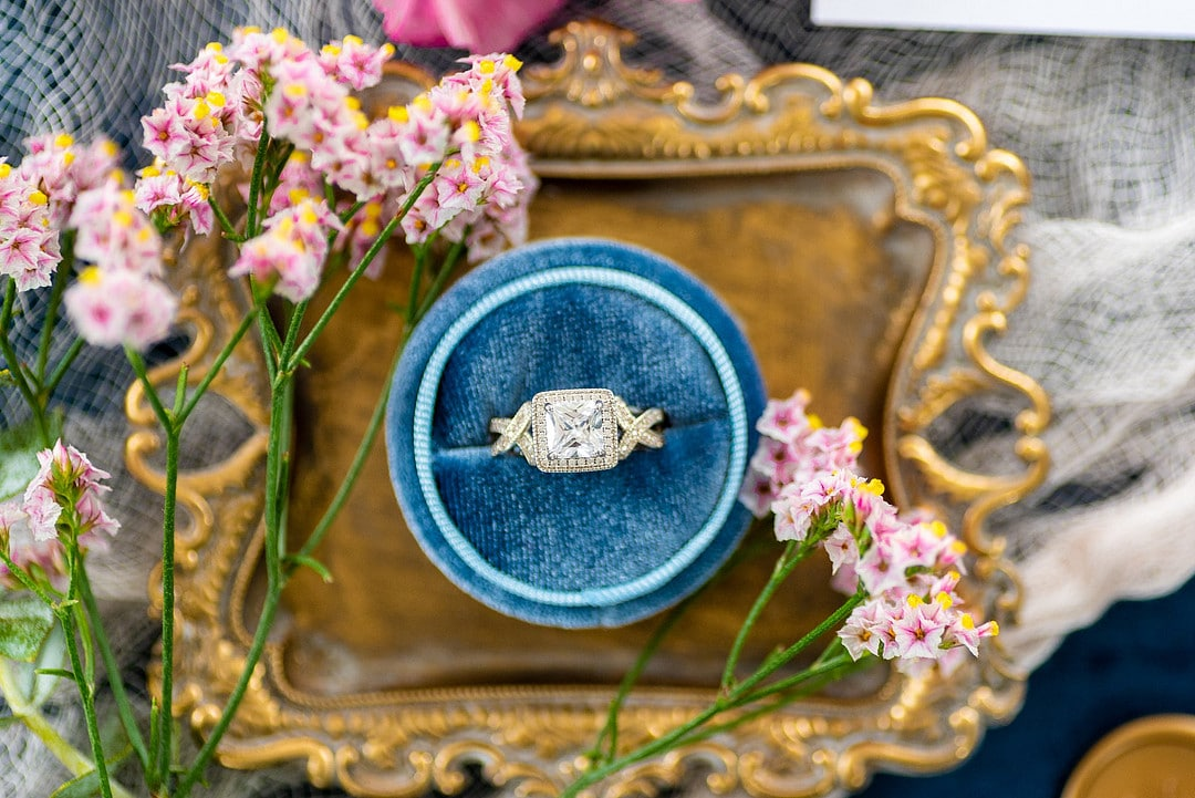 wedding ring in blue velvet ring box on old tray surrounded by sprig of small flowers
