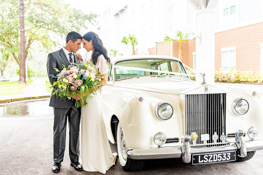bride and groom stand touching foreheads with bouquet next to classic rolls royce car