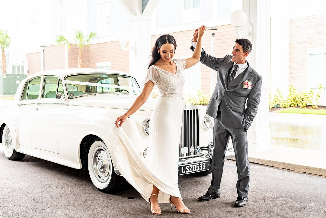 bride and groom in front of rolls royce car bride holds grooms hand and lifts up the hem of her dress