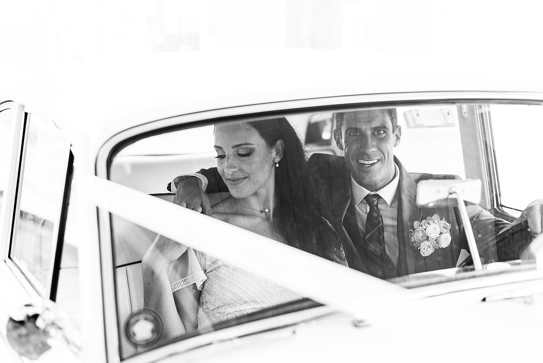 black and white shot from outside of car looking in at bride and groom in front seat of classic car with grooms arm over bride