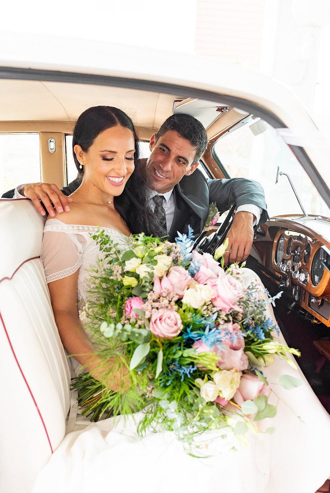 bride looks down at big bouquet while groom sits behind her looking at the bride inside the front seat of classic car