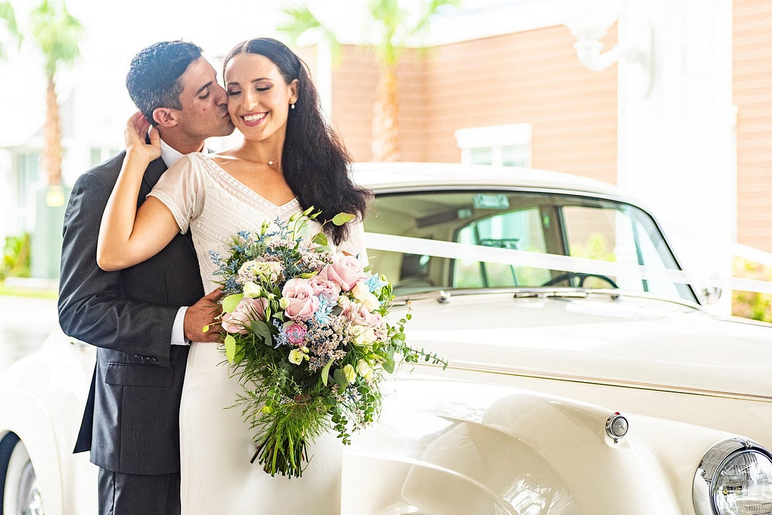 bride stands in front of groom with bouquet as he holds her waist and kisses her cheek next to classic car
