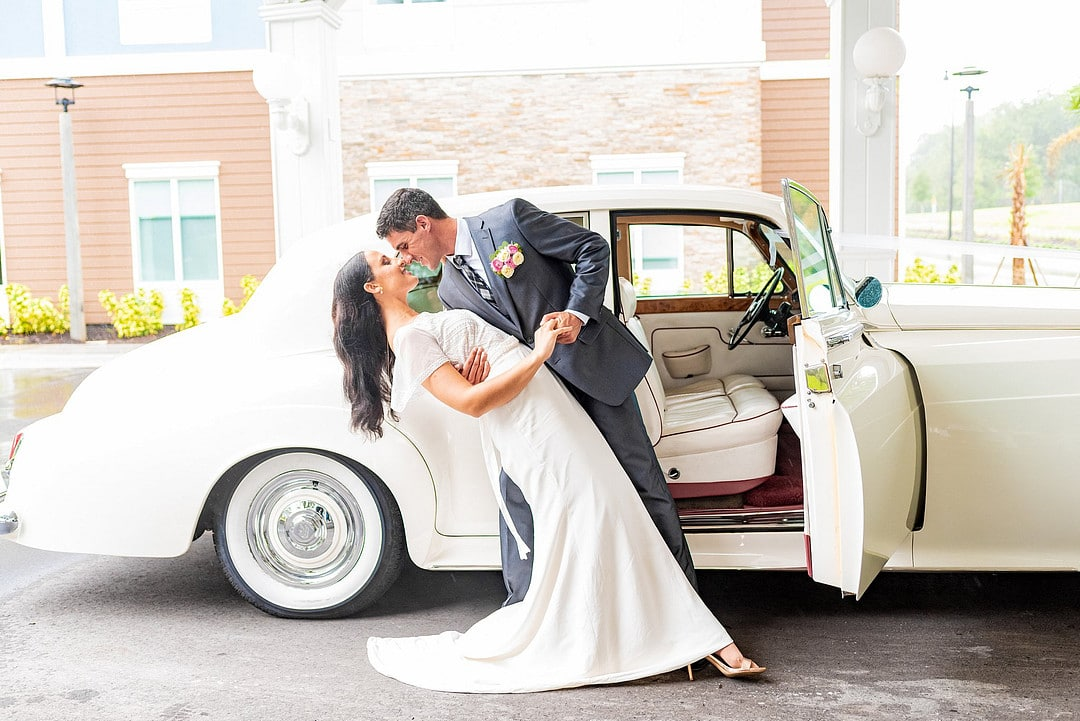 groom dipping bride face to face in front of open car door of rolls royce outside wedding venue