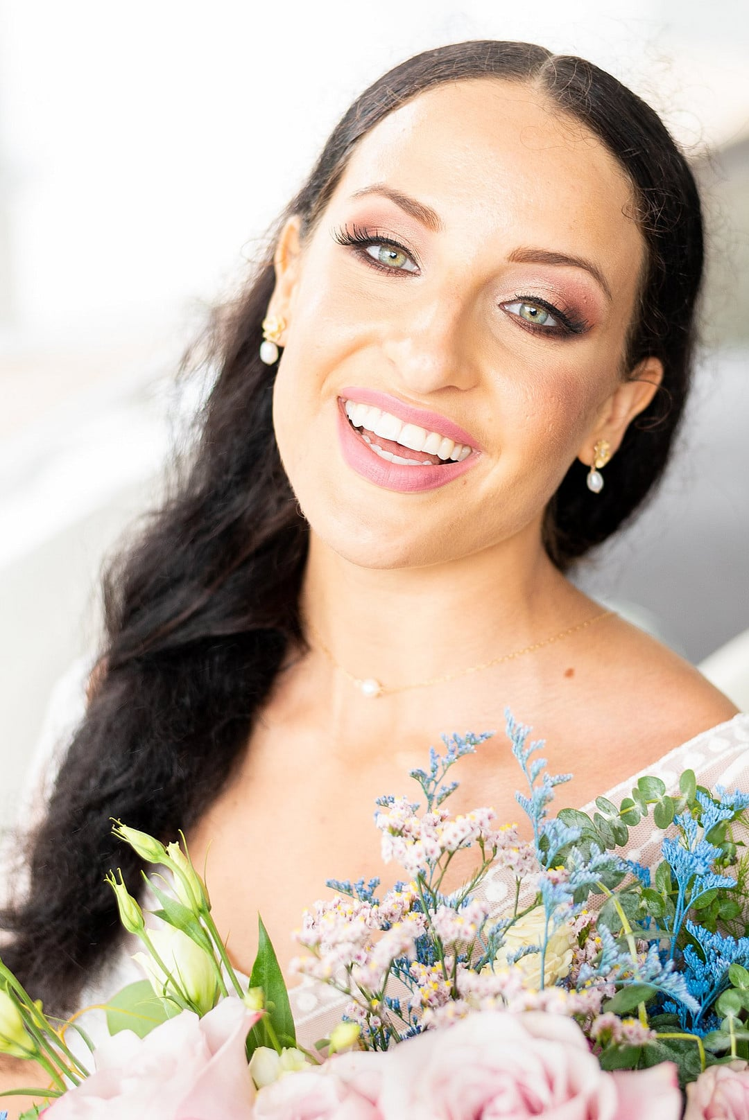 bride smiles big with light colored makeup and dark hair parted down the middle with her bouquet close to her chest