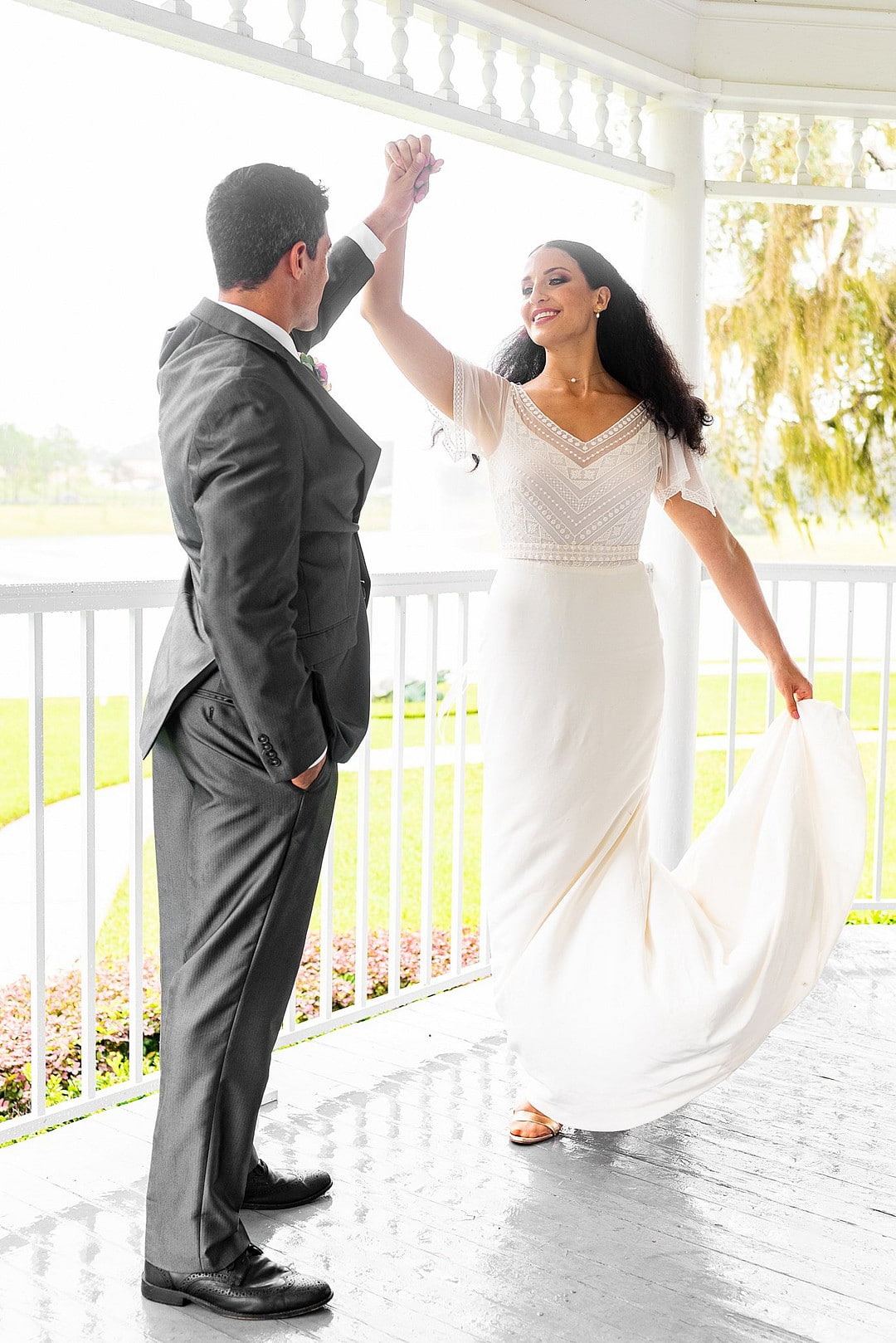 groom twirls bride around on the porch of wedding venue during dusty pastel inspired wedding shoot