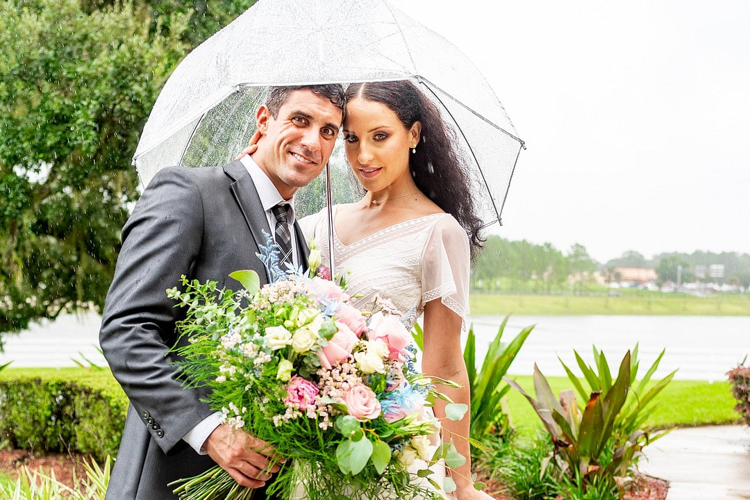 bride and groom under umbrella in front of body of water outside while it rains and groom holds big bouquet in front of them