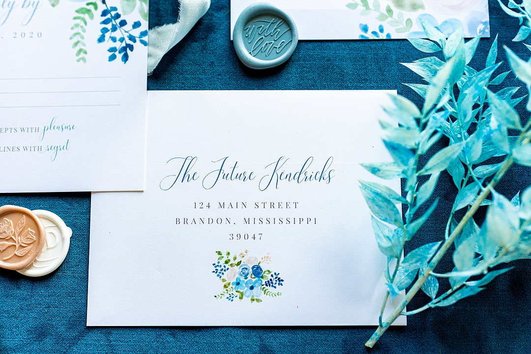 dusty pastel inspired wedding invitation hand calligraphy with greenery next to it