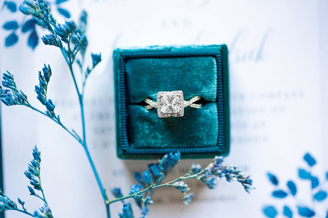 wedding ring in teal colored velvet ring box on top of wedding invitation with piece of blue colored filler floral