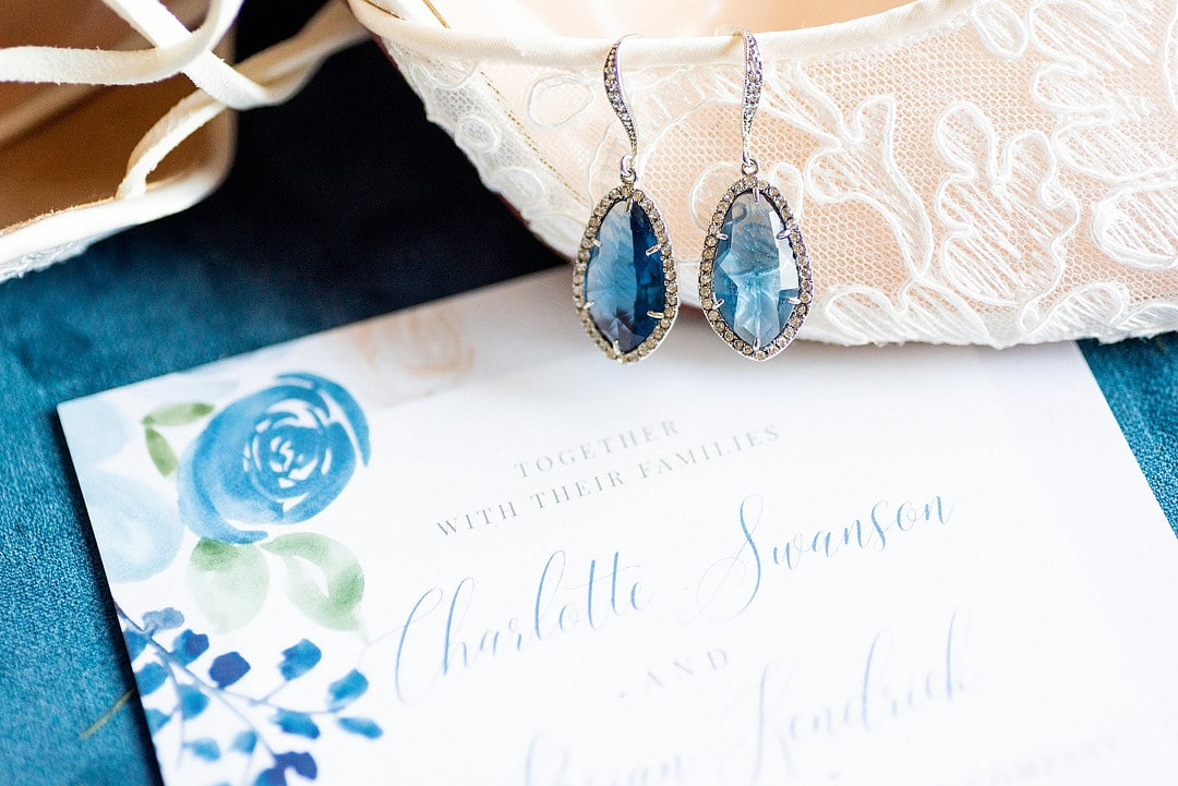 close up of calligraphy wedding invitation and lace heel with blue tear drop earring hanging off of it
