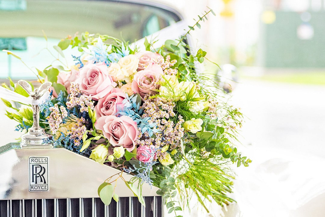 bridal bouquet with pink and blue colors sits on top of the hood of a rolls royce car